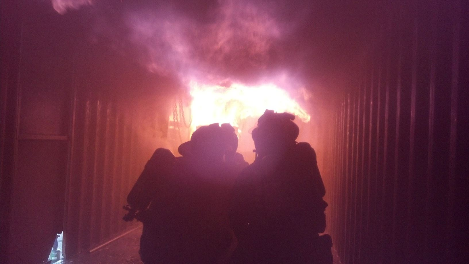 Two firefighters silhouetted against a raging fire.